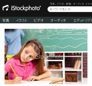 黒板と生徒を背景に教室の机に座る小学生の女の子